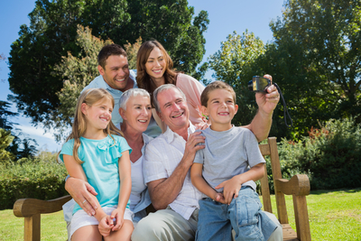 Multi generation family sitting on a bench taking photo of themselves