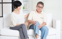 Asian old man knee pain, sitting on sofa with wife at home. Chinese family, senior retiree indoors living lifestyle.