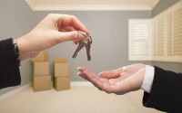 Woman Handing Over the House Keys To A New Home Inside Empty Grey Colored Room.
